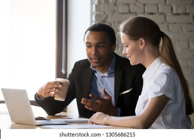 Two multiracial workers sit at office desk near laptop discussing business issues together, man and woman employee negotiate at workplace, look at computer, cooperating speak or explain ideas