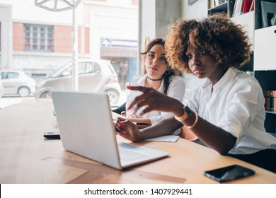 two multiracial young women analysing a project in coworking studio – freelance, resourceful, concentration