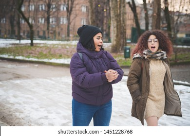 two multiracial young women walking and talking in the street – friendship, movement, cheerful