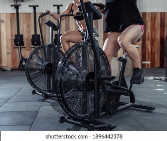 Two muscular athletic women exercising on air bikes at the gym. Functional training class working out