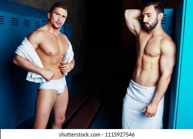 two muscular handsome men after workout and shower  in the locker room