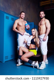 two muscular men and a young blond woman in the locker room