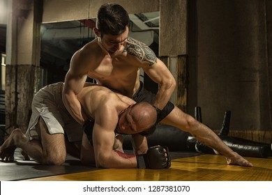 Two muscular sportsmen wearing gloves and shorts training in fight without rules in gym. Mixed martial fighter standing on knee and keeping with hands his rival standing on all four and resisting.