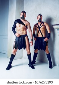 two muscular striptease dancers wearing leather costumes and masks, in the studio