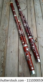 Two musical instruments, a bassoon on a wooden old surface.