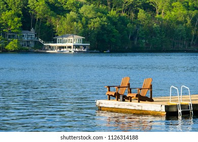 Two Muskoka chair sitting on a wood dock facing a calm lake. Across the water is a white cottage nestled among green trees.