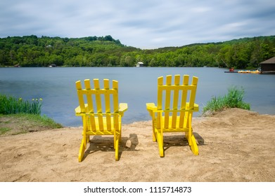 Two Muskoka chairs on a sandy beach facing a lake. Across the calm water cottages are nestled among green trees.