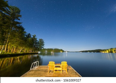 Two Muskoka chairs sitting on a wooden dock facing a calm lake at night. The sky over the cottages is illuminated by stars.