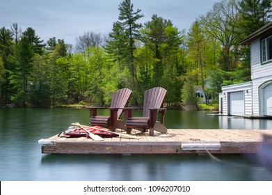 Two Muskoka chairs sitting on a wood dock facing a lake. Behind the chairs is a white cottage. There are some life jackets and canoe paddles in front the chairs. A canoe is tied to the dock.