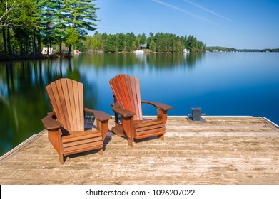 Two Muskoka chairs sitting on a wood dock facing a lake. Behind the chairs are cottages nestled among green trees. There are no clouds in the sky.
