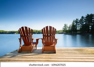 Two Muskoka chairs sitting on a wood dock facing a lake. Across the calm water are cottages nestled among green trees. There are no clouds in the sky.