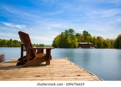 Two Muskoka chairs sitting on a wood dock facing a lake. Across the calm water is a brown cottage nestled among green trees. There is a boat dock on the water in front of the cottage.