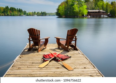 Two Muskoka chairs sitting on a wood dock facing a lake. Across the calm water is a brown cottage nestled among green trees. Some life jackets and canoe paddles are on the dock.