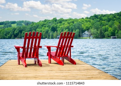 Two Muskoka chairs sitting on a wood dock facing a calm lake. Across the water is a cottage nestled among green trees. Clouds are visible in the blue sky