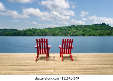 Two Muskoka chairs sitting on a wood dock facing a calm lake. Across the water, cottages are nestled among green trees. Clouds are visible in the blue sky