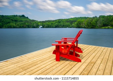 Two Muskoka chairs sitting on a wood dock facing a calm lake. Across the water is a blue cottage nestled among green trees. Clouds are visible in the blue sky