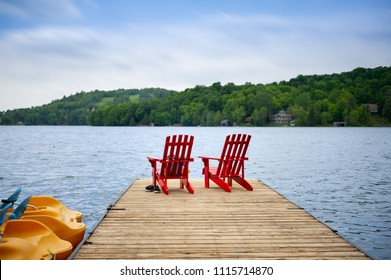 Two Muskoka chairs sitting on a wood dock facing a lake. Across the calm water, cottages are nestled among green trees.