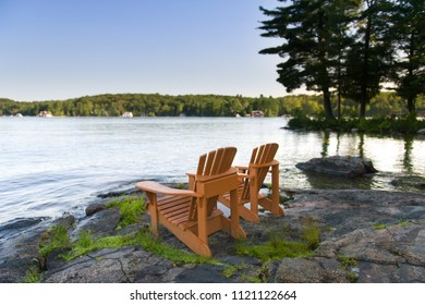 Two Muskoka chairs sitting on a rock formation facing a calm lake. Across the water are cottages nestled among green trees.