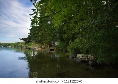 Two Muskoka chairs sitting on a wood dock facing a calm lake.