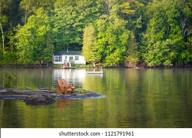 Two Muskoka chairs sitting on a rock formation facing a calm lake. Across the water is a white cottage nestled among green trees. There is a boat dock on the water in front of the cottage.