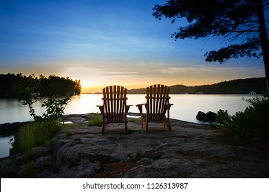 Two Muskoka chairs sitting on a rock formation facing a calm lake at sunset.