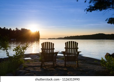 Two Muskoka chairs sitting on a rock formation facing a calm lake at sunset. Sun beams are visible