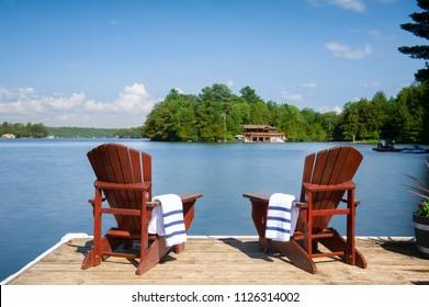 Two Muskoka chairs sitting on a wood dock facing a calm lake. Across the water is a cottage nestled among green trees. On the chairs there are towels.