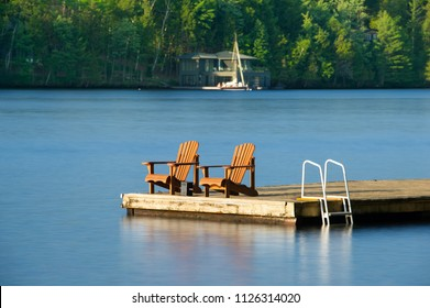 Two Muskoka chairs sitting on a wood dock facing a calm lake. Across the water is a cottage nestled among green trees. There is a sailing boat docked.