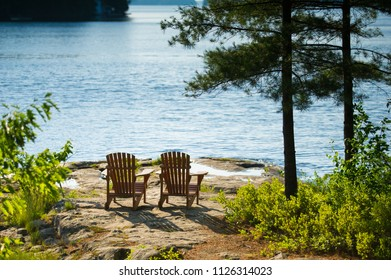 Two Muskoka chairs sitting on a rock formation facing a calm lake.