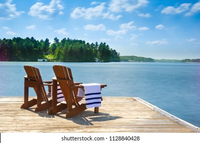 Two Muskoka chairs sitting on a wood dock facing a calm lake. Across the water is a white cottage nestled among green trees. On the chairs there are towels.