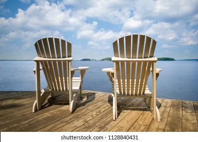 Two Muskoka chairs sitting on a wood dock facing a calm lake. Across the water is a white cottage nestled among green trees.