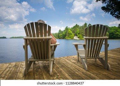 Two Muskoka chairs sitting on a wood dock facing a calm lake. Across the water is a white cottage nestled among green trees. A young woman is sitting on one of the Adirondack chairs.