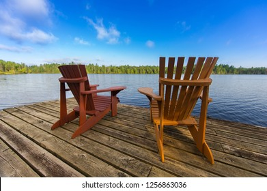 Two Muskoka chairs sitting on a wood dock facing a lake.