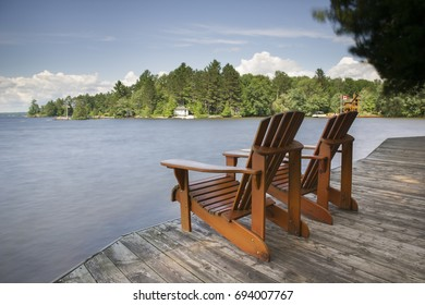 Two Muskoka chairs sitting on a wood dock facing a lake. Across the calm water are cottages nestled among green trees. Canada flag is visible