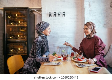 Two Muslim Friends Enjoying food while sitting in cafe