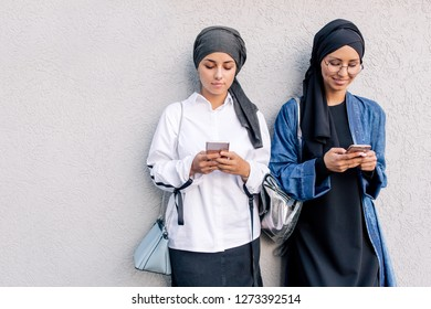 Two Muslim girlfriends in everyday hijab leaning on the wall sitting on the Internet holding phones