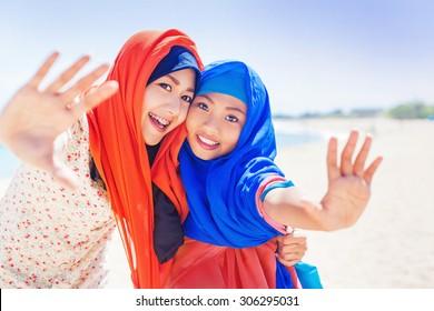 two muslim girls smiling at camera