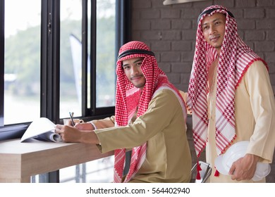 Two of Muslim, Middle-East men with traditional dress and head wear working around counter bar in office space at Cafe