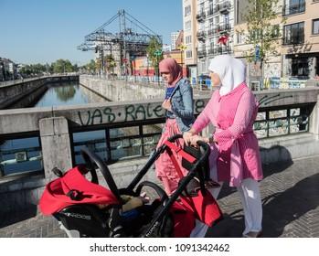 Two Muslim women walk across a bridge in Brussels, Belgium. The bridge separates the Muslim district of Molenbeek from the rest of the city. 10/05/2018