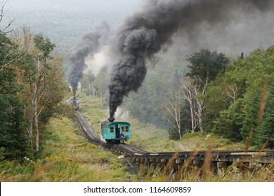 Two narrow gauge cog rail steam Trains climbing up  at Mount Washington summit during good weather conditions