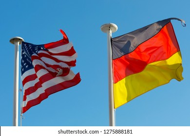Two National Flags of both United States of America and Germany waves against clear blue sky background