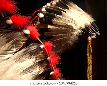 Two Native American Chief's feathered headdresses or  bonnets are on a black background