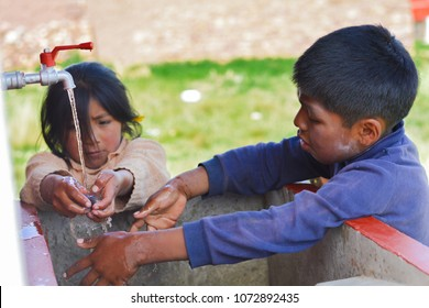Two native american children washing potato outside.