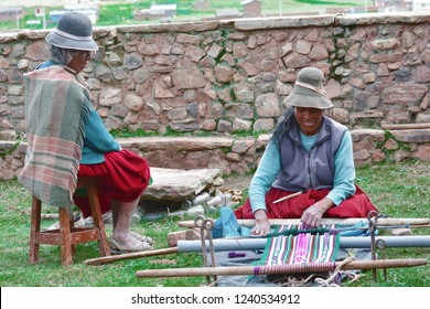 Two native american women weaving traditional aymara carpet in the countryside.