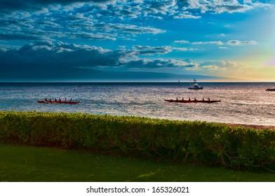 Two native Hawaiian boats rowing past at sunset on Maui, Hawaii, USA