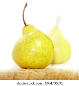Two naturally crooked pear on a white background with a wooden base. Soft focus view.