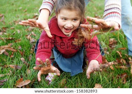Two Naughty Sisters Young Girls Playing With Muddy Hands In A Park With Green Grass And