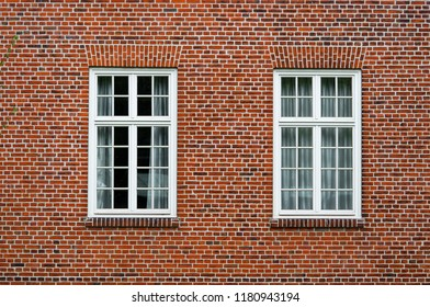 Two neighboring windows with white frames in a urban red bricks clinker house.