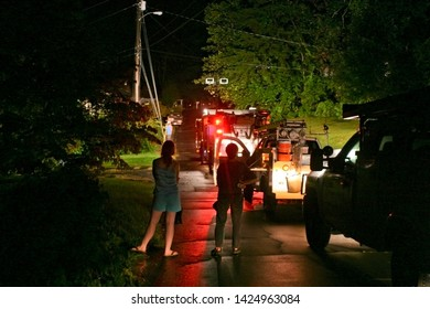 Two neighbors watch as their dark neighborhood street fills with flashing utility vehicles, equipment, and workers who have come to fix their power outage after a nighttime storm