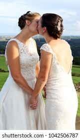 Two new brides kissing on their wedding day , beautiful Yorkshire landscape in the background, both wearing traditional white dresses , they are happy and in love.